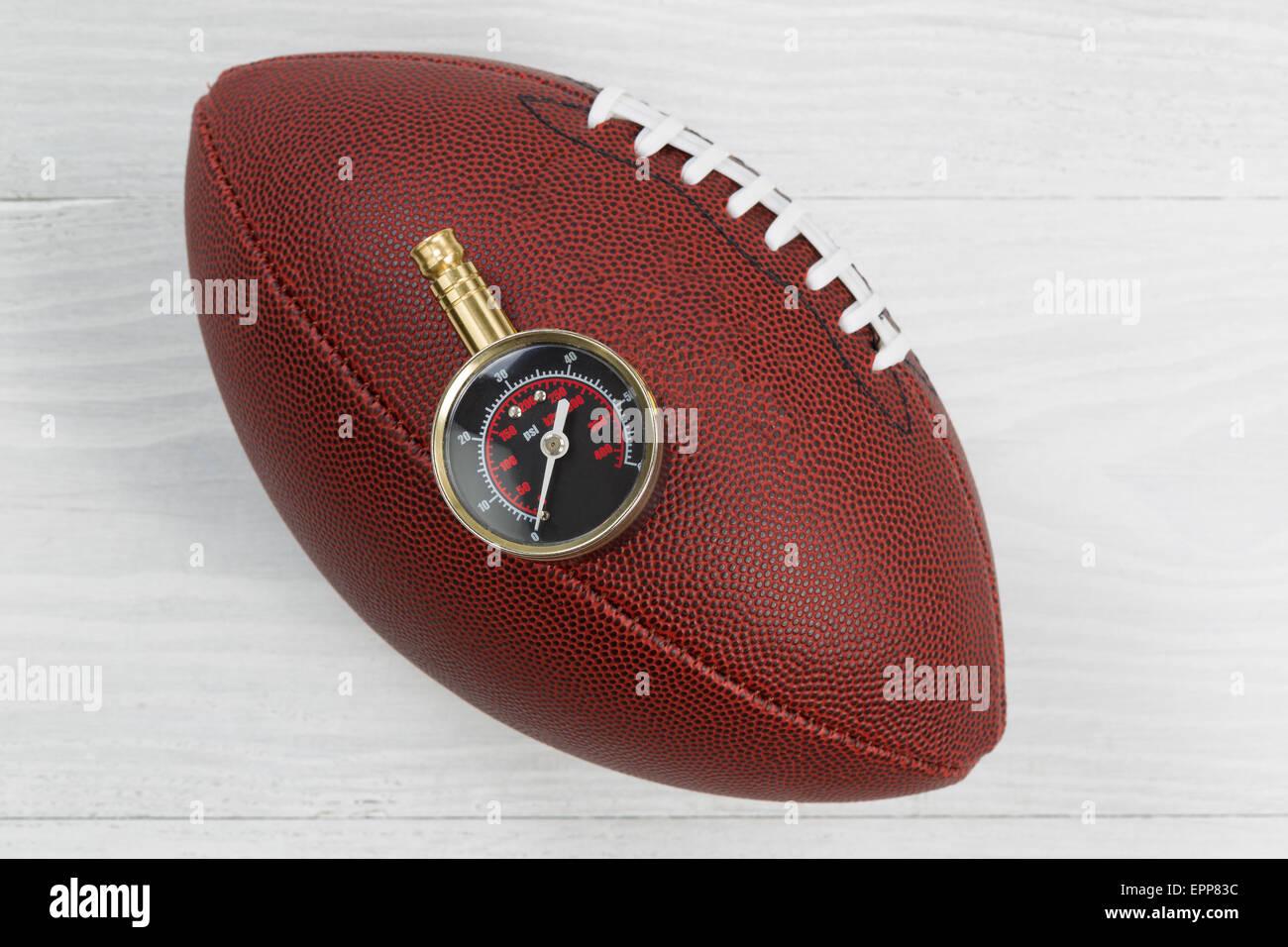 Close up d'America football con aria il manometro sulla parte superiore della sfera con rustico in legno di Immagini Stock