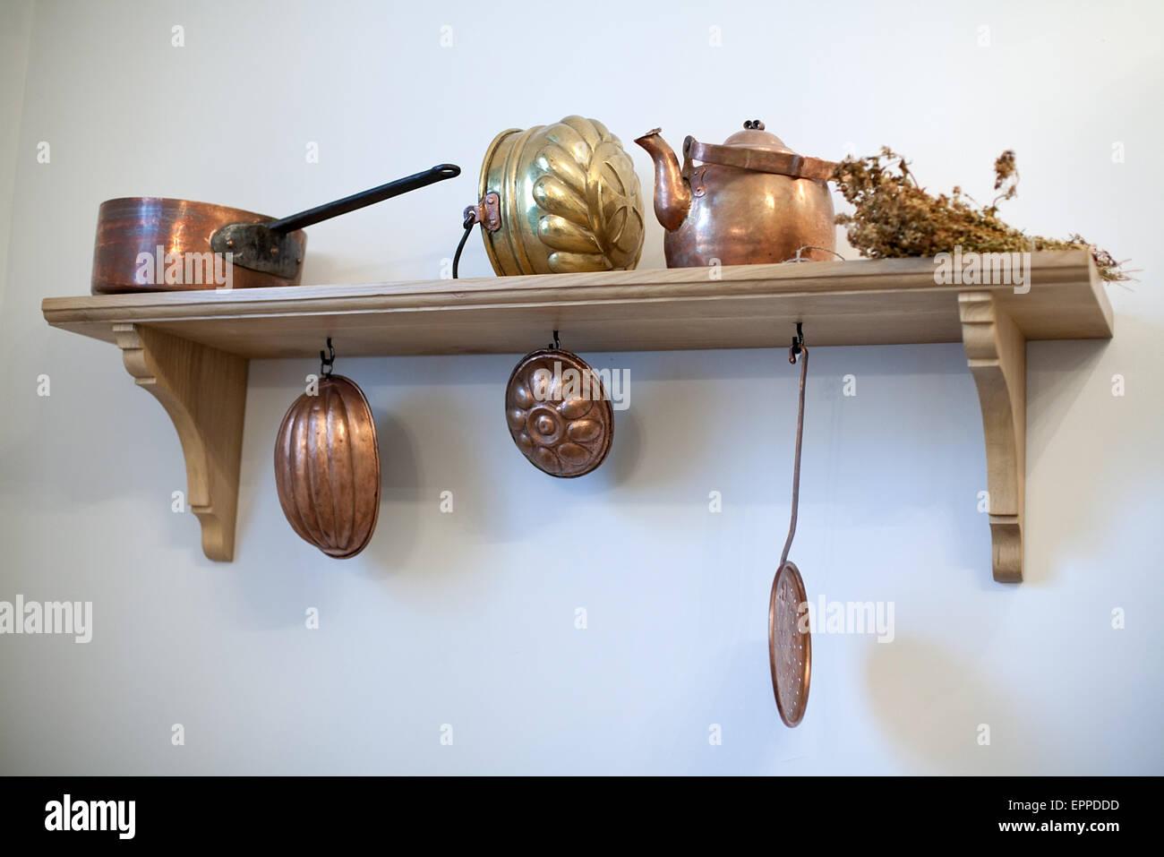 Mensola da cucina con vecchi utensili di rame sul muro bianco sullo ...