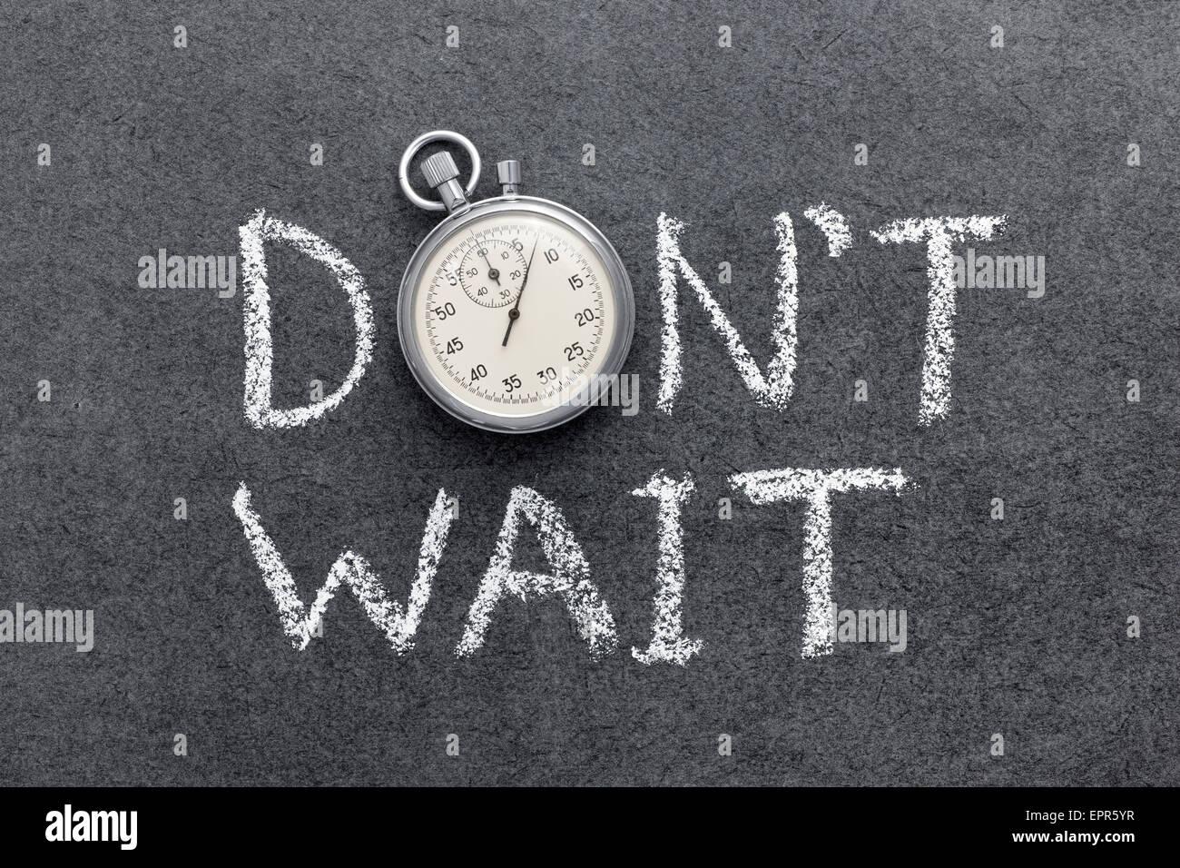 Non aspettare una frase scritta a mano sulla lavagna con vintage cronometro preciso utilizzato al posto di o Immagini Stock