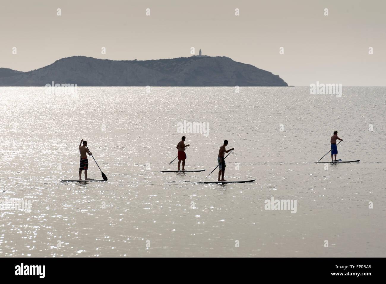 Sagome di Stand Up Paddle surfisti (paddle boarders) al tramonto. Costa di Ibiza Immagini Stock