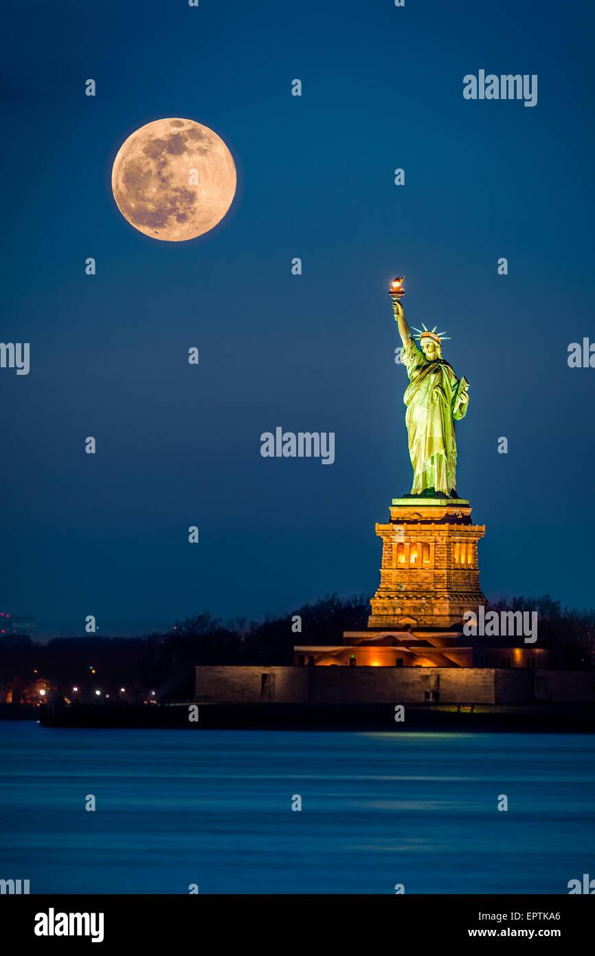 La Statua della Libertà e un crescente supermoon nella città di New York Foto Stock