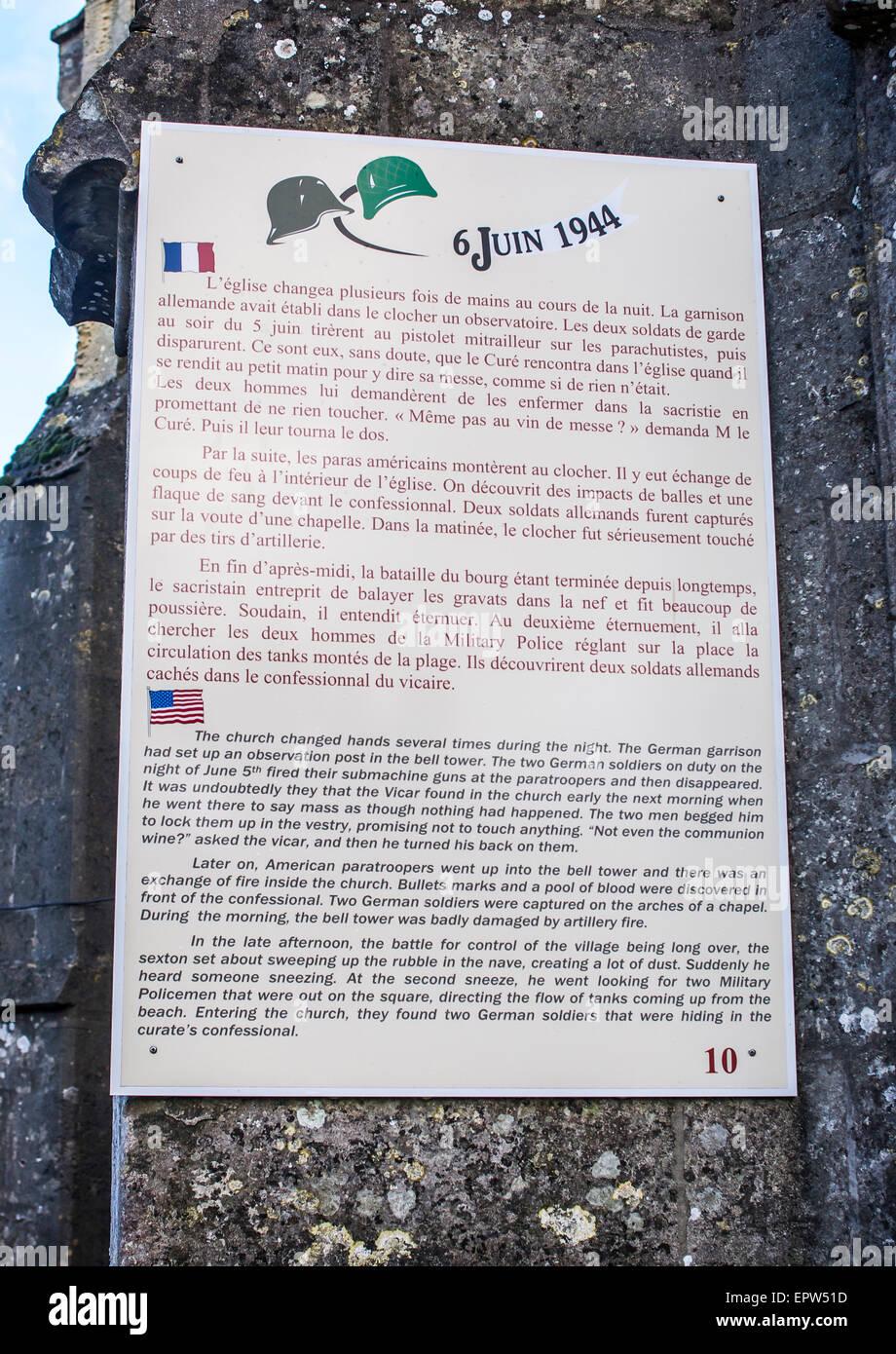 La placca montato sulla parete laterale della eglise (chiesa) nella storica Guerra Mondiale II D-Day invasione villaggio Immagini Stock