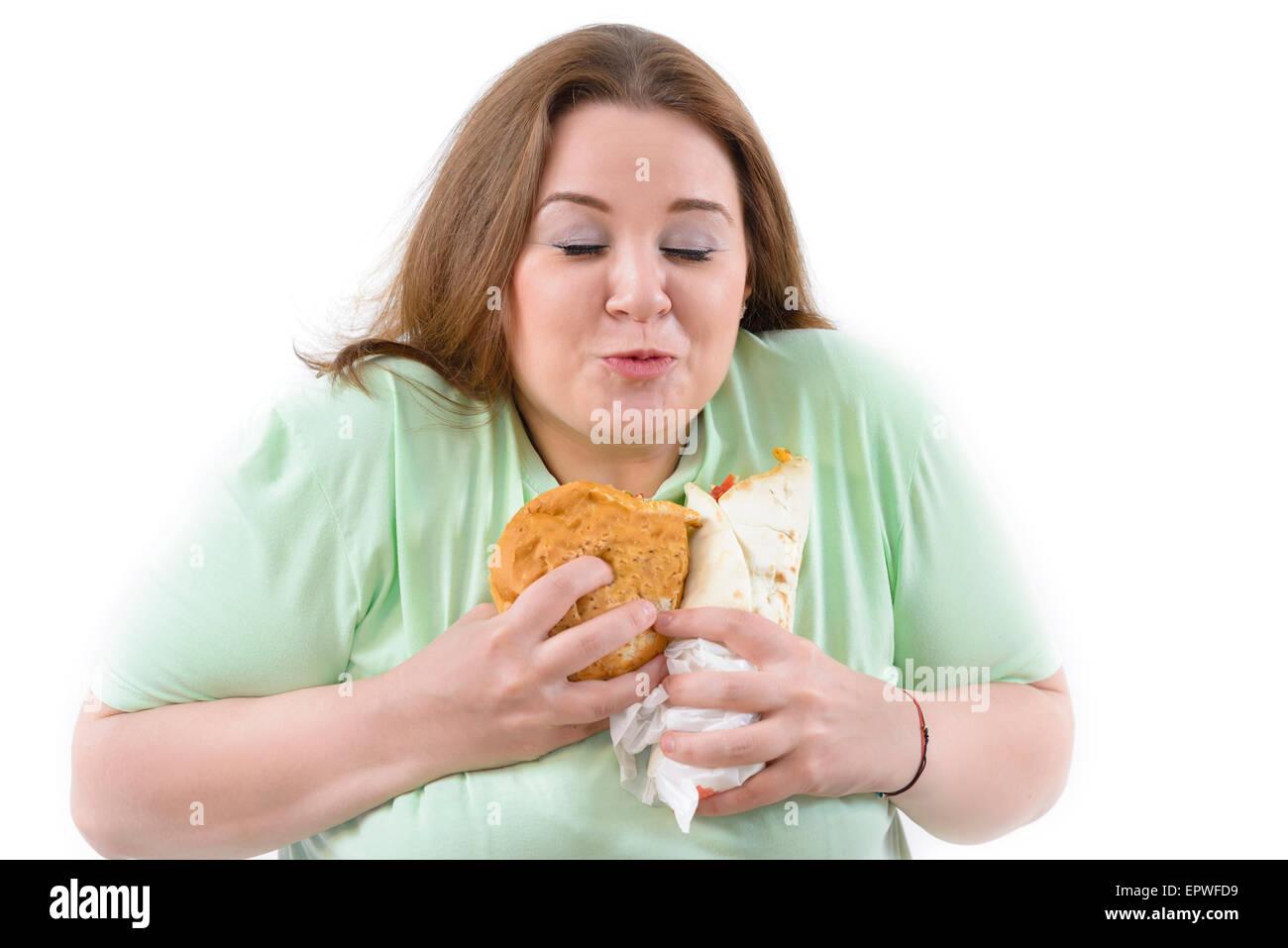 Corpulento donna avente la dipendenza da cibo malsano. Felice Tiene alcuni alti calorie cibo. Immagini Stock