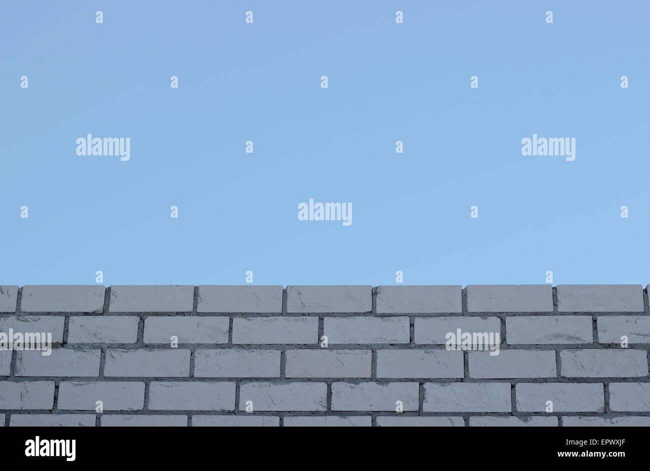 La tessitura di un bianco muro di mattoni il cielo blu sfondi Immagini Stock