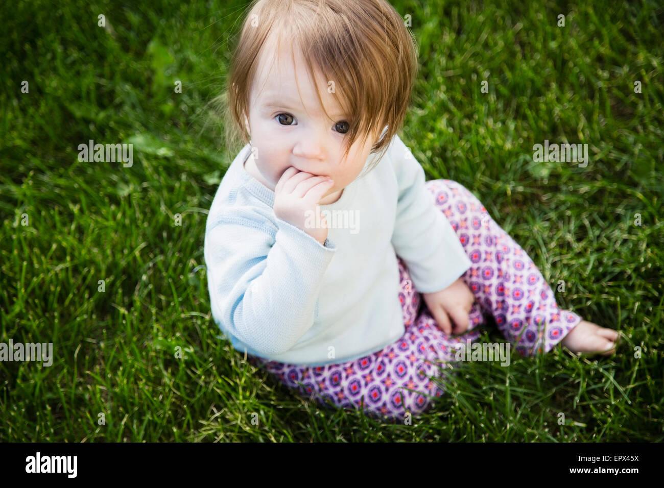 Ritratto di bambina (6-11 mesi) con la mano in bocca Immagini Stock