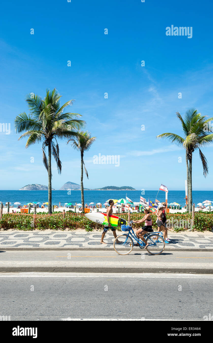 RIO DE JANEIRO, Brasile - 08 Marzo 2015: brasiliani a piedi e in bici con tavole da surf sulla passeggiata sul lungomare Immagini Stock