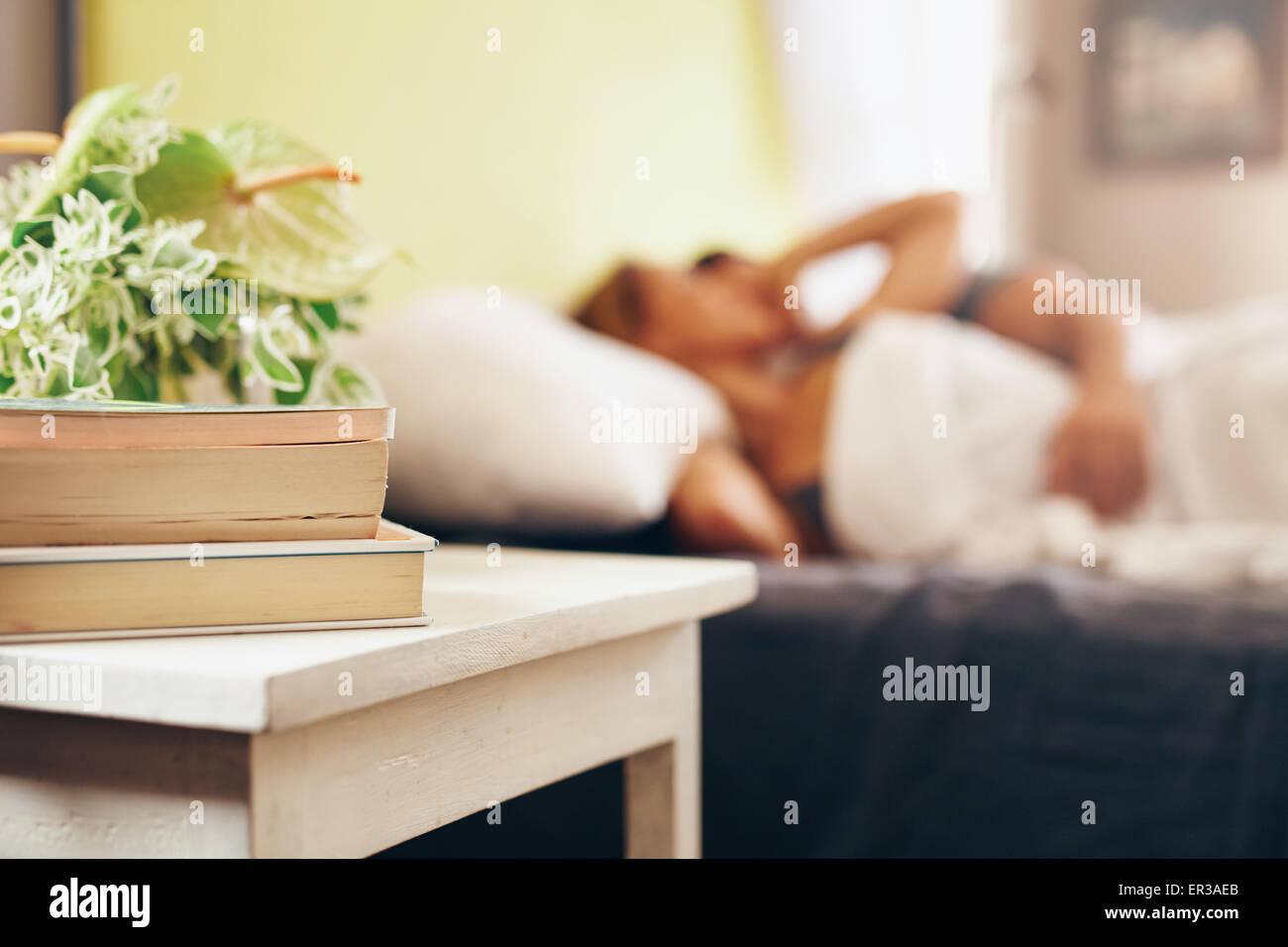 Tavolino con libri e fiori dal letto in camera da letto. Giovane dormire tranquillamente sul letto. Immagini Stock