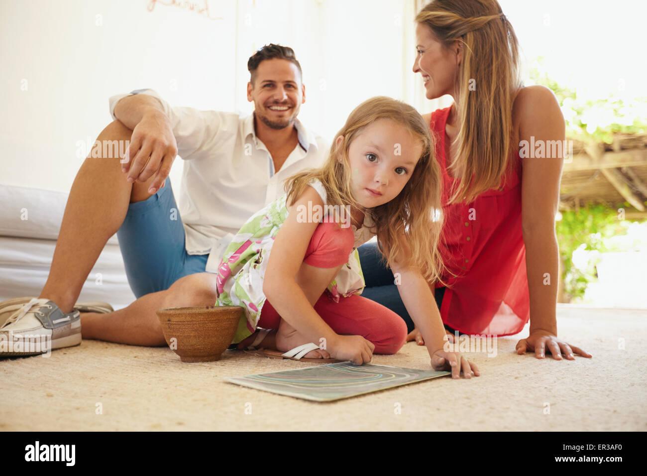 Piscina colpo di carino bambina dipinto con i suoi genitori seduti dietro di lei. Famiglia seduta sul pavimento Immagini Stock
