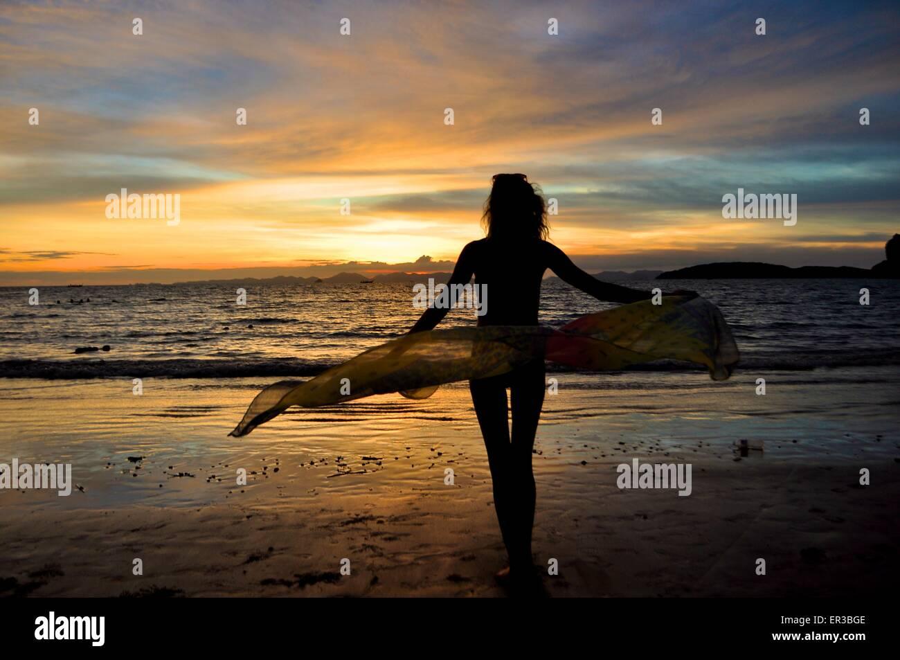 Silhouette di donna in spiaggia con un sarong Immagini Stock