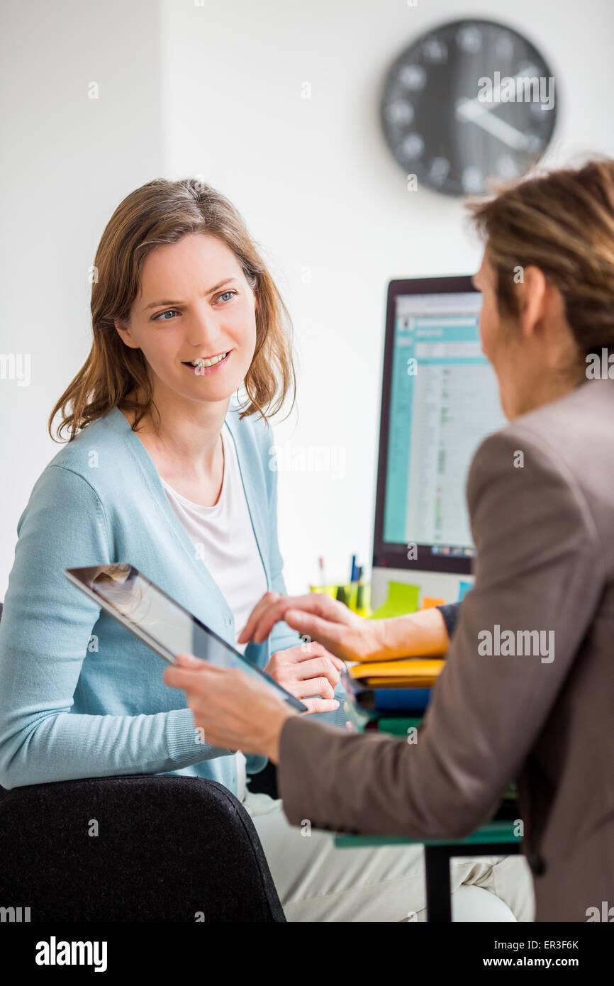 Le donne a discutere sul lavoro. Immagini Stock
