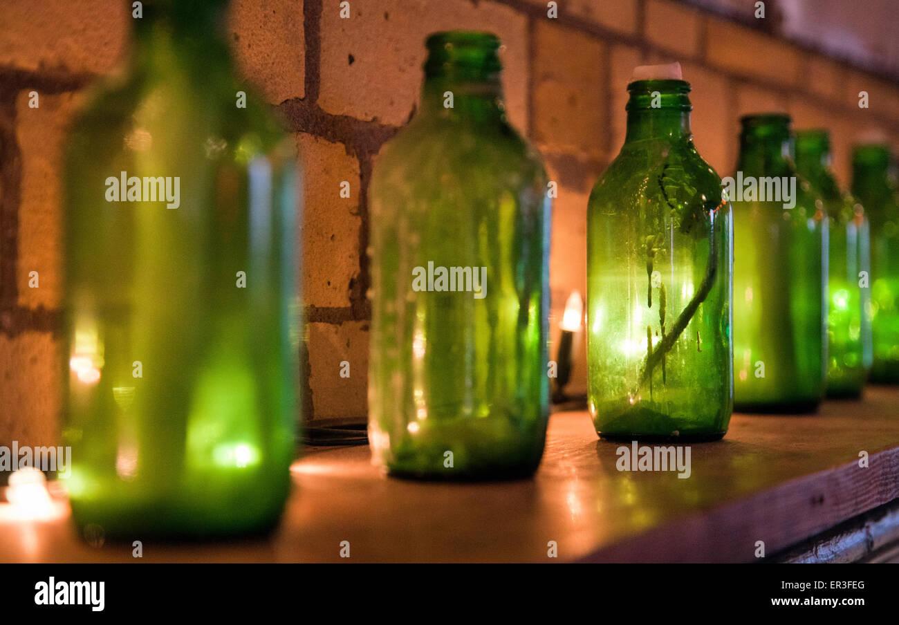 Bottiglie verdi con candele usate per l illuminazione foto