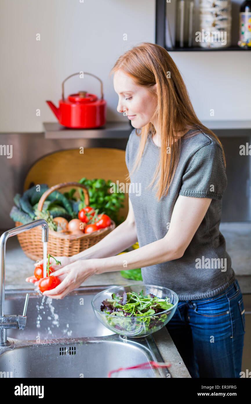 La donna il lavaggio della verdura. Immagini Stock