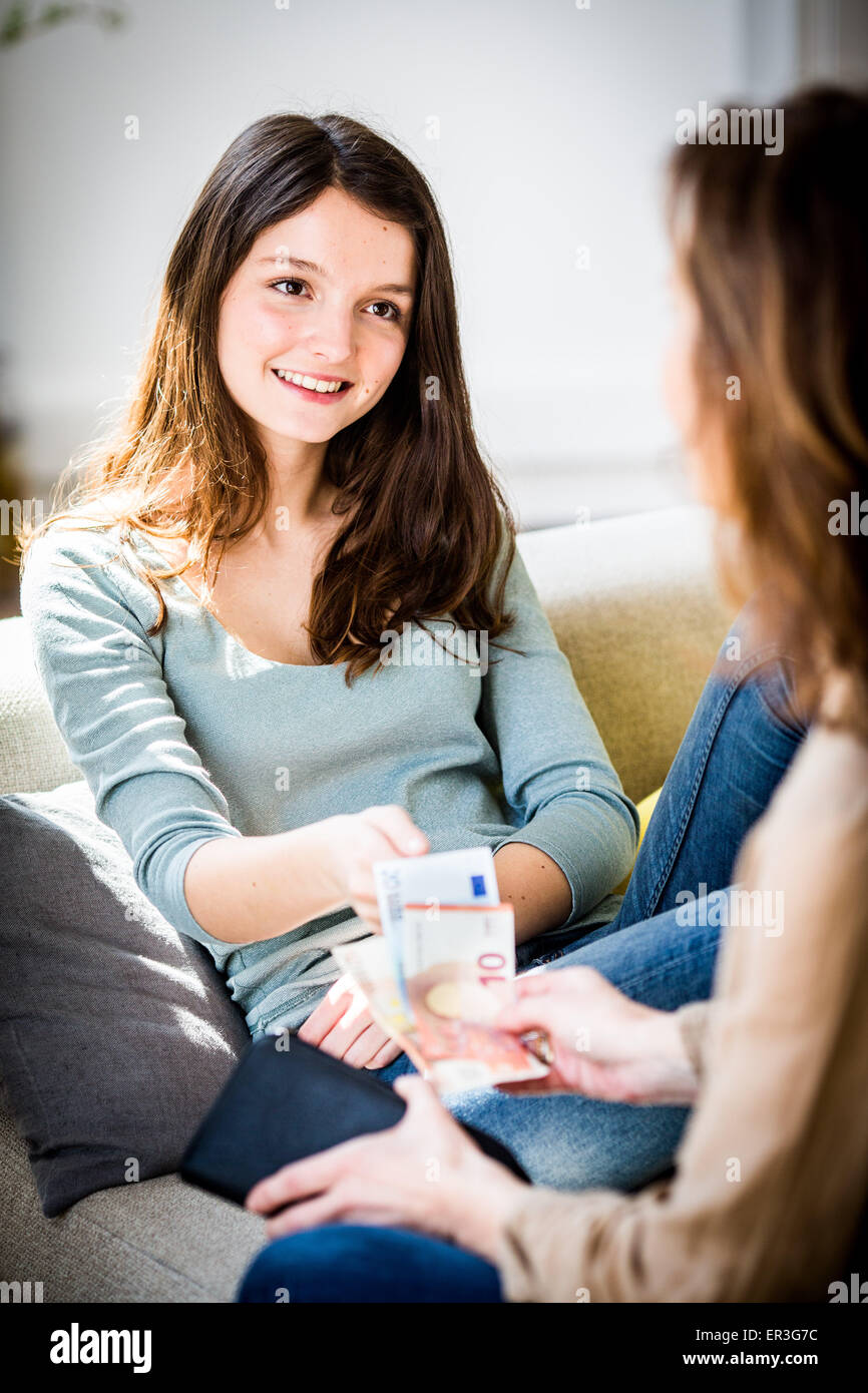 Madre dando la sua figlia pocket money. Immagini Stock
