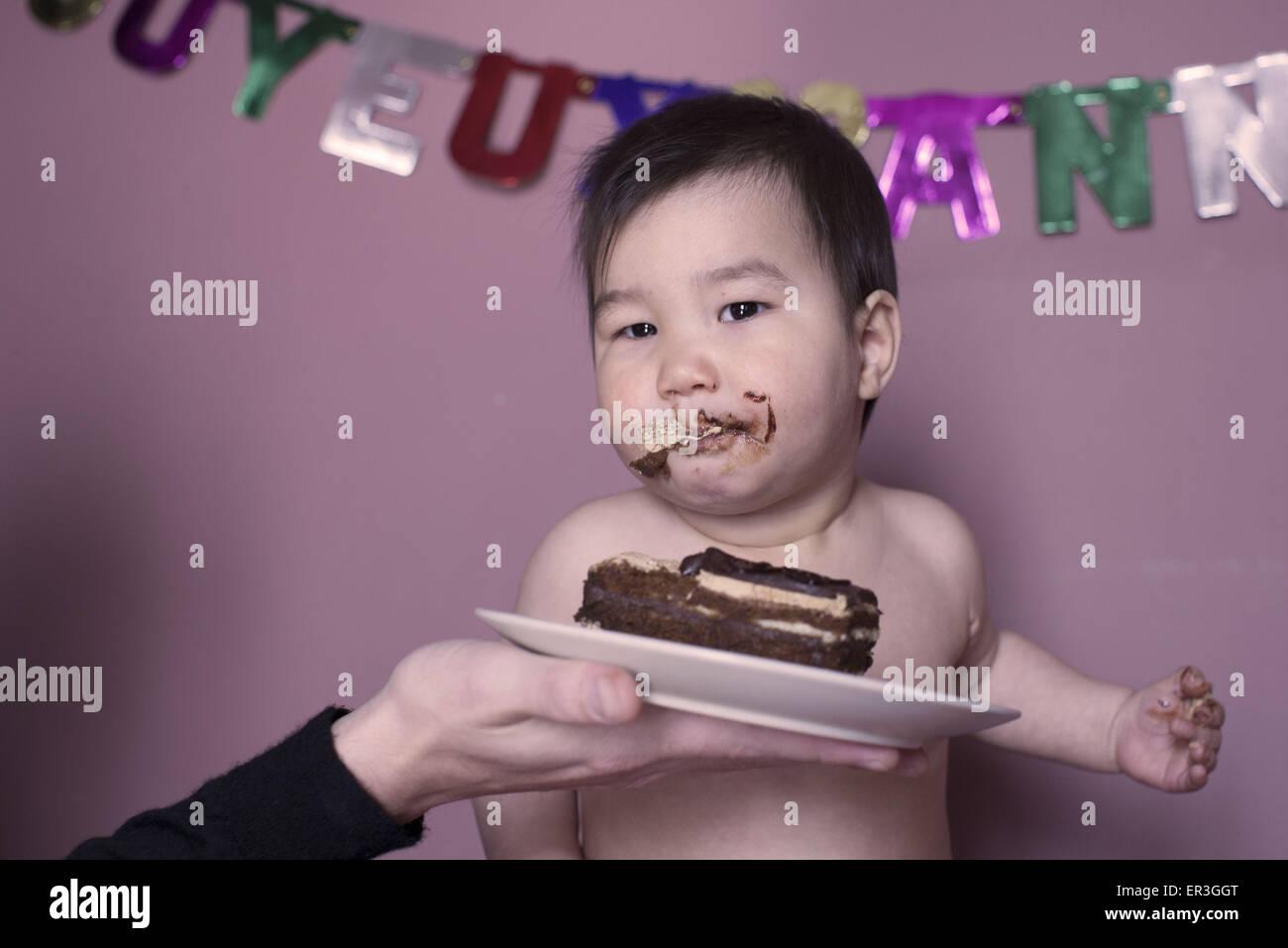 Baby mangiare la torta di compleanno Immagini Stock