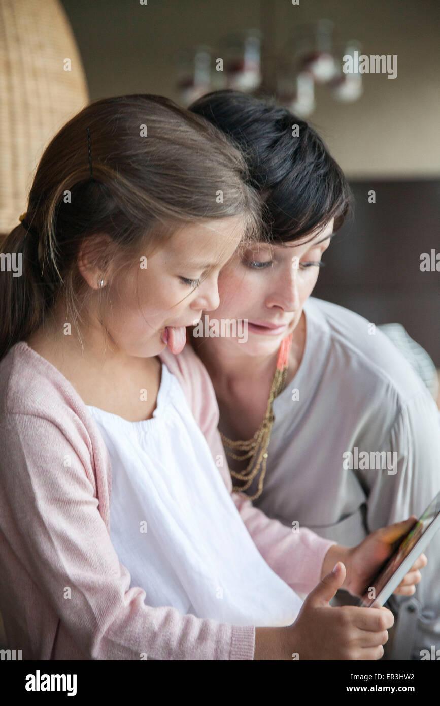 Madre e figlia giovane con tavoletta digitale e facendo facce buffe Immagini Stock