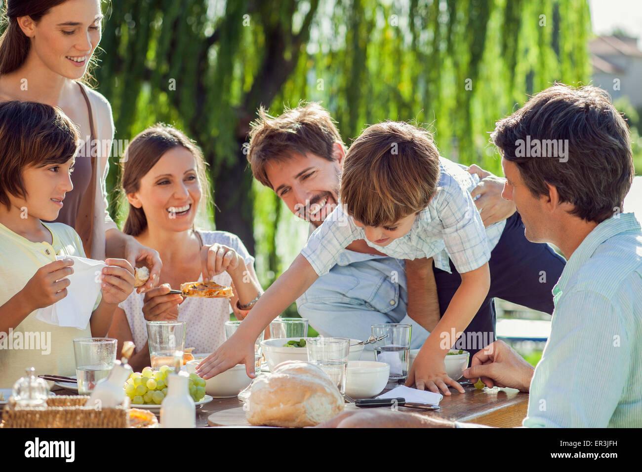 Famiglia gustando la prima colazione insieme all'aperto Immagini Stock
