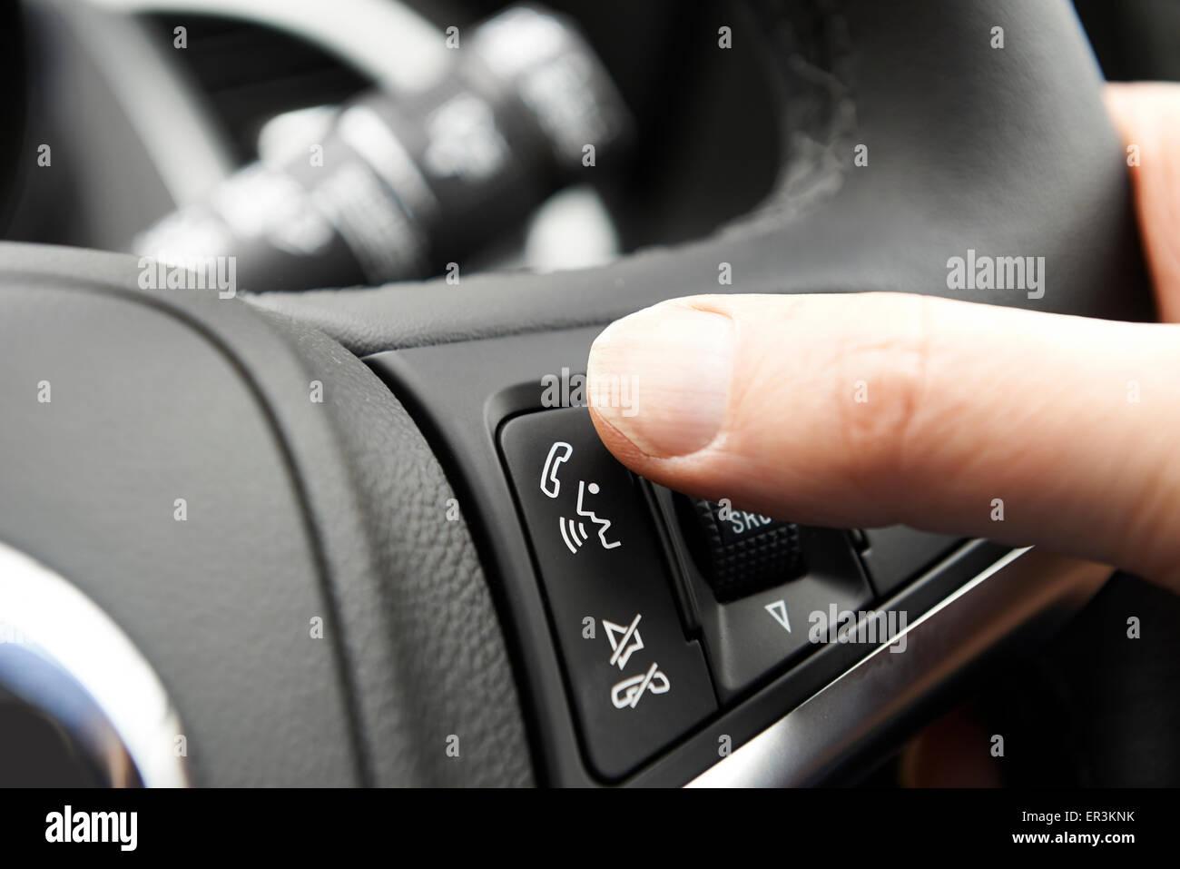 Stretta di mano premendo auto controllo Bluetooth sul volante Immagini Stock