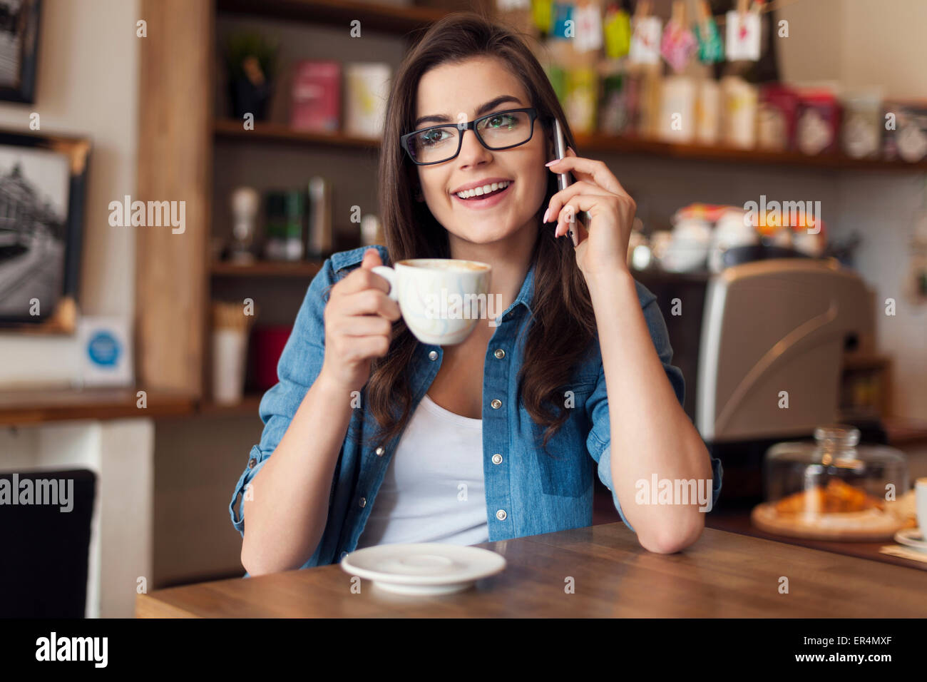 Sorridente giovane donna parla al telefono cellulare presso il cafe. Cracovia in Polonia Immagini Stock