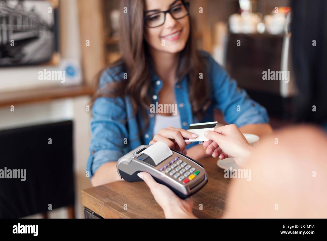Donna sorridente pagando per un caffè con carta di credito. Cracovia in Polonia Immagini Stock