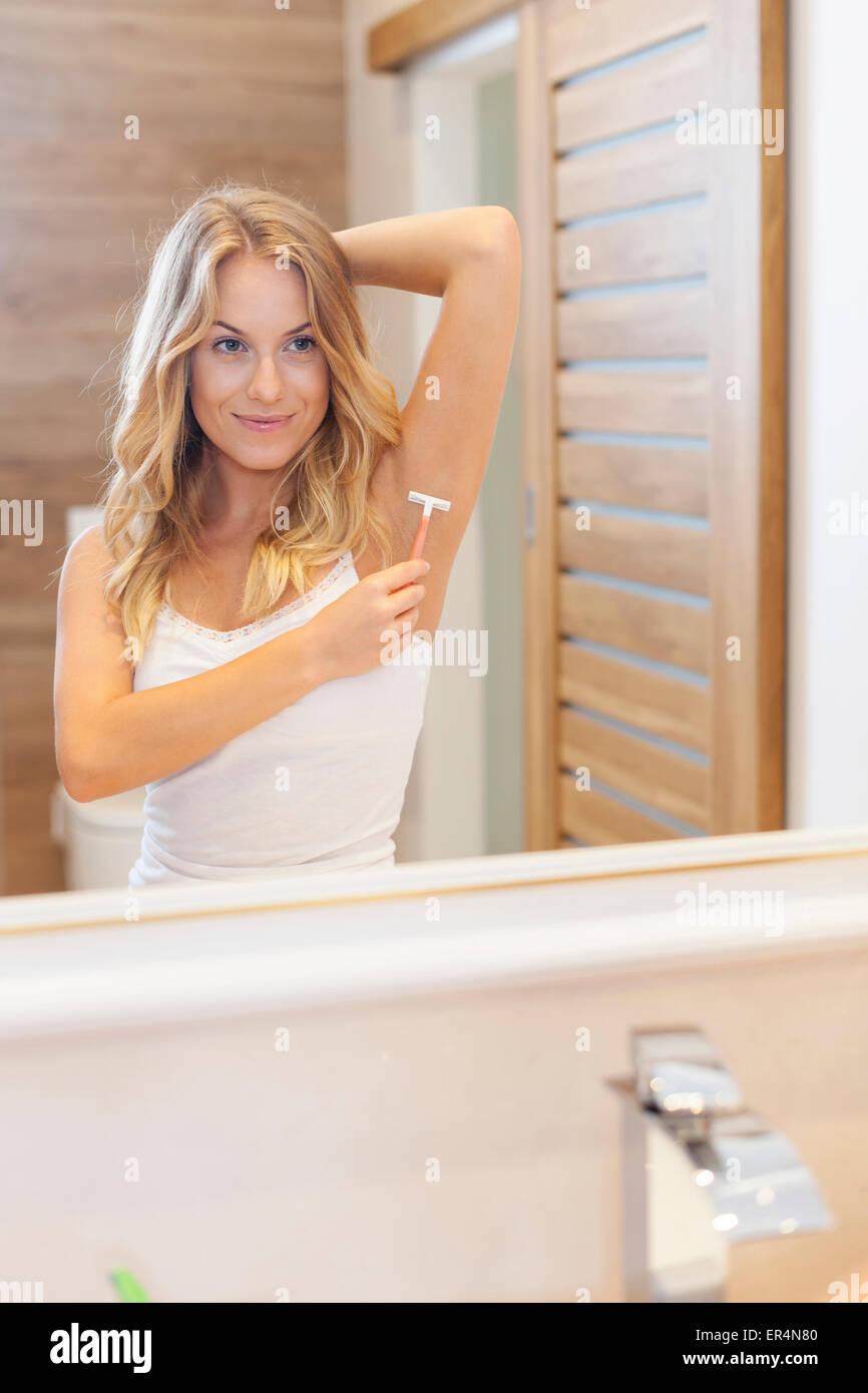La donna la rasatura delle ascelle in bagno. Debica, Polonia Immagini Stock