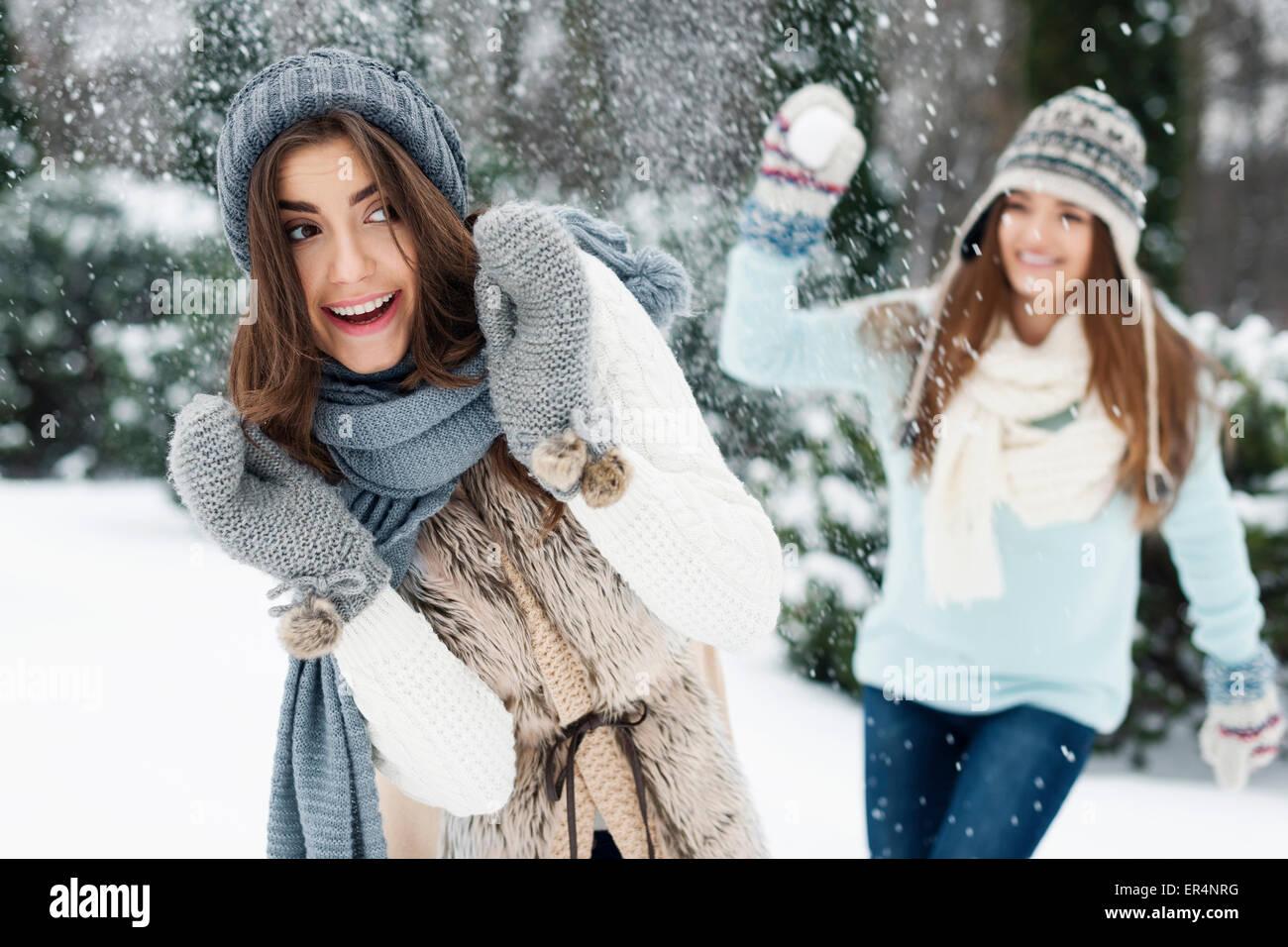 Le giovani donne hanno divertimento durante la lotta con le palle di neve. Debica, Polonia Immagini Stock
