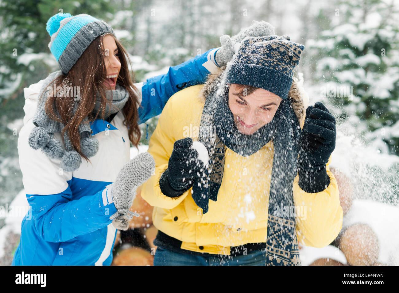 Coppia giovane divertirsi durante la lotta con le palle di neve. Debica, Polonia Immagini Stock