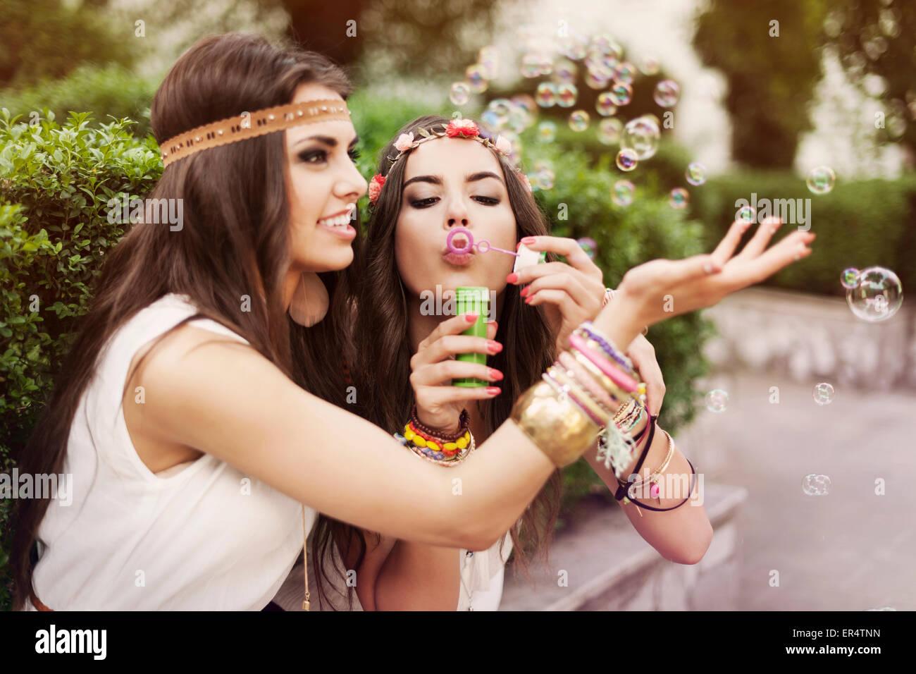 Due belle ragazze hippie soffiare bolle. Cracovia in Polonia Immagini Stock