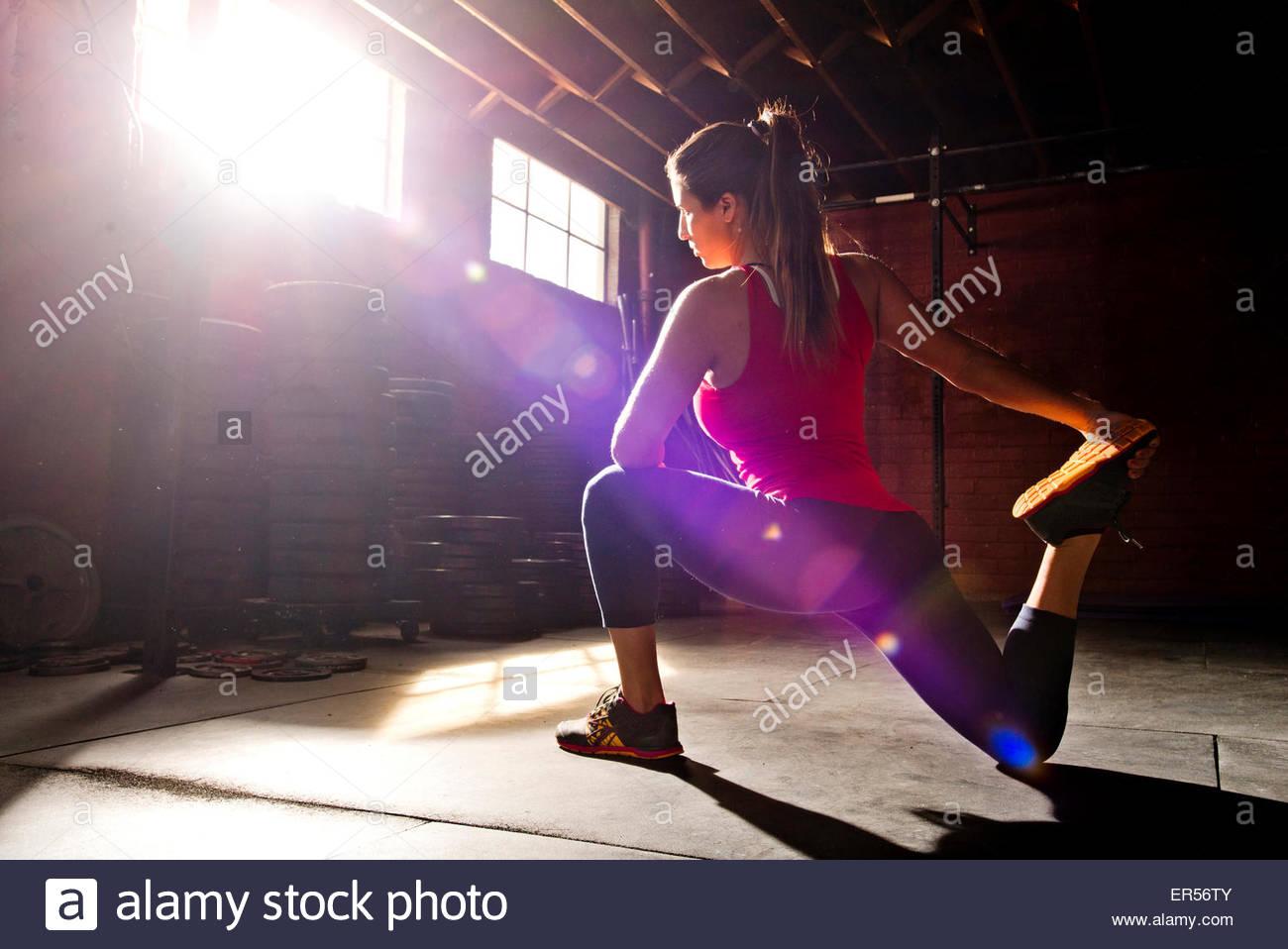 Un atleta donna si allunga in una palestra crossfit. Immagini Stock