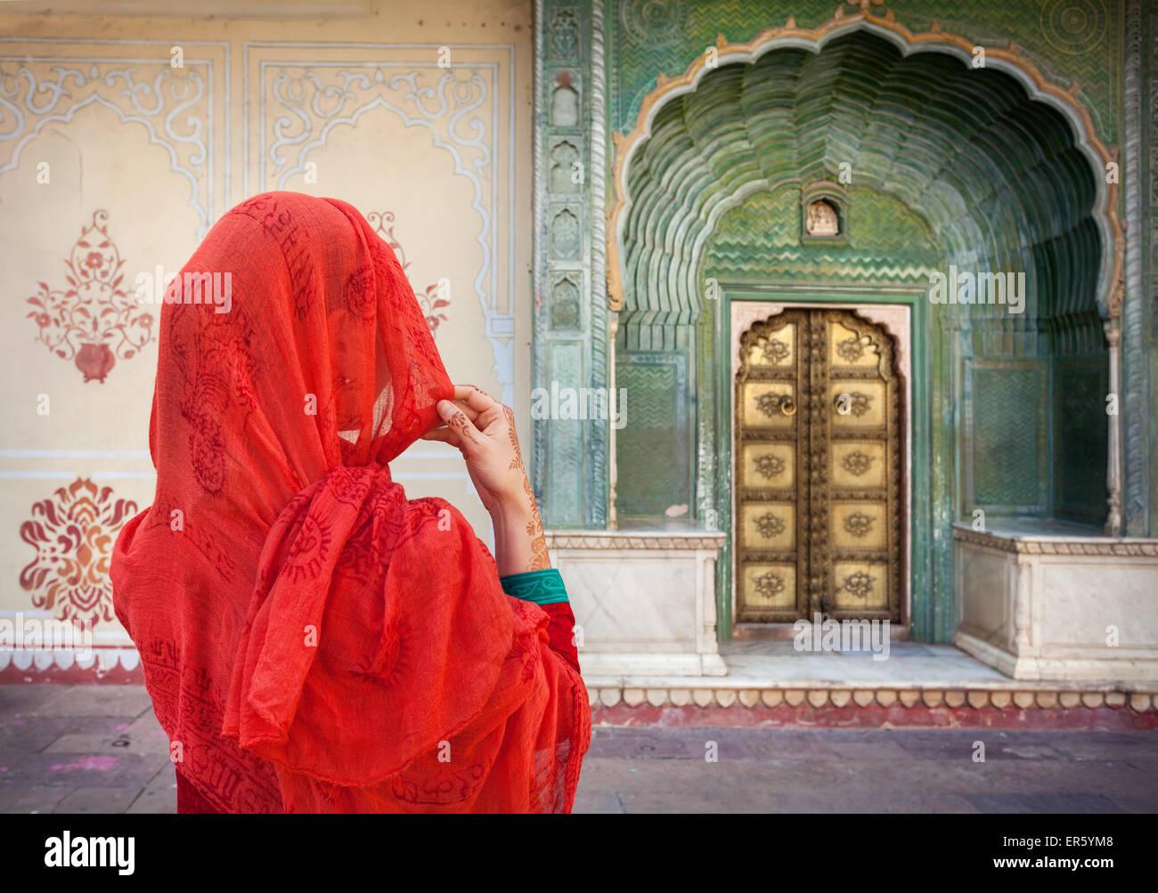 La donna in sciarpa rossa guardando il cancello verde porta in palazzo di città di Jaipur, Rajasthan, India Immagini Stock