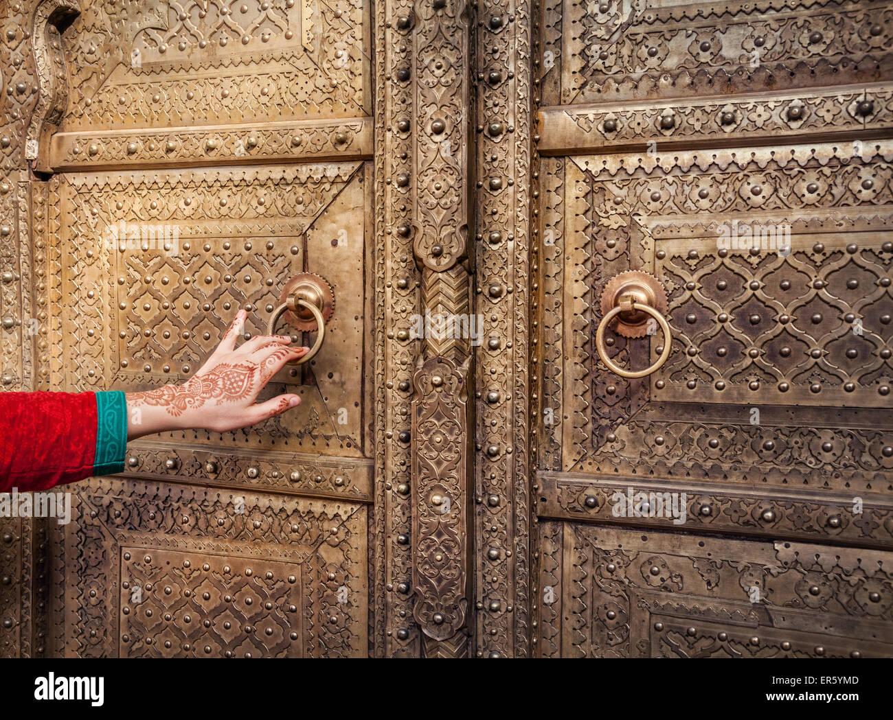 Donna con la mano di pittura henné apertura porta d'oro nel palazzo di città di Jaipur, Rajasthan, Immagini Stock