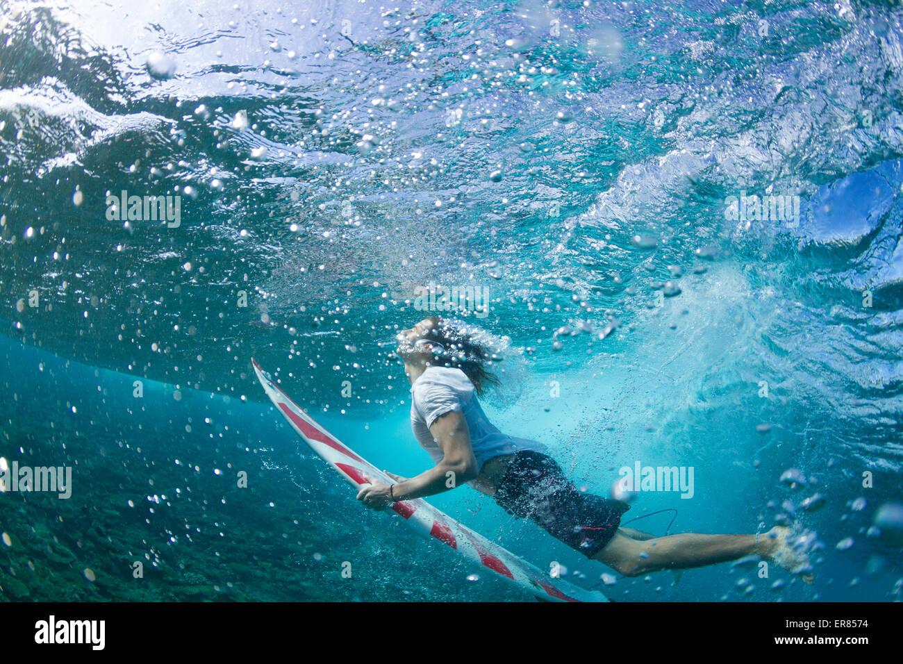 Vista subacquea di un surfista duck immersione sotto un'onda Immagini Stock