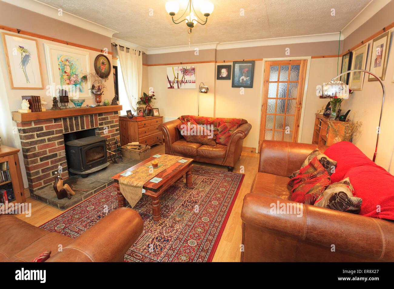 Lounge in casa inglese con tre divani in pelle e legno bruciatore ...