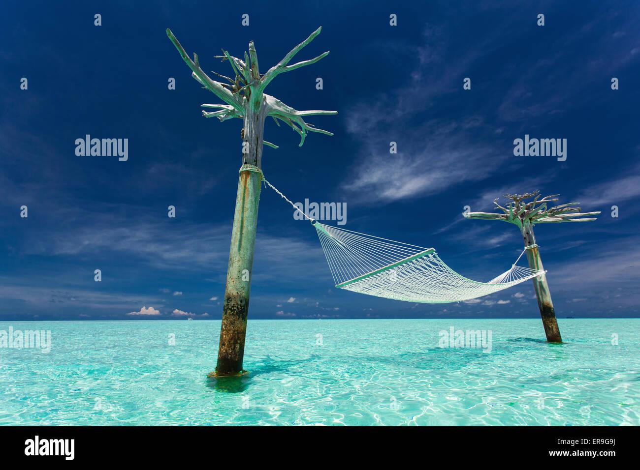 Svuotare over-acqua amaca nel mezzo della laguna tropicale delle Maldive Immagini Stock