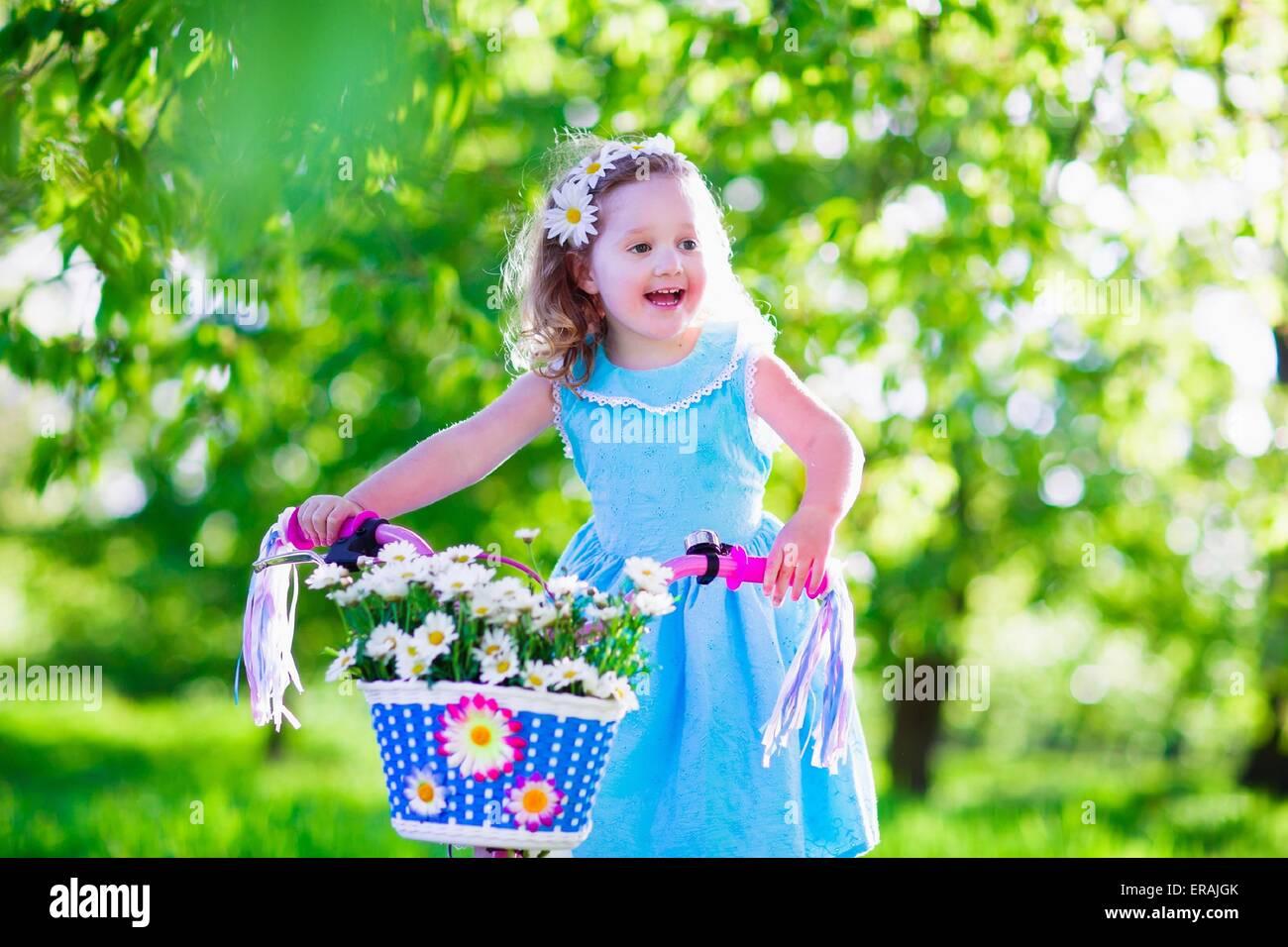 e4a7c0e6b753 Bambino felice in sella ad una bicicletta. Carino kid bike all esterno.  Piccola ragazza in un abito blu su una bicicletta rosa con fiori a  margherita nel ...