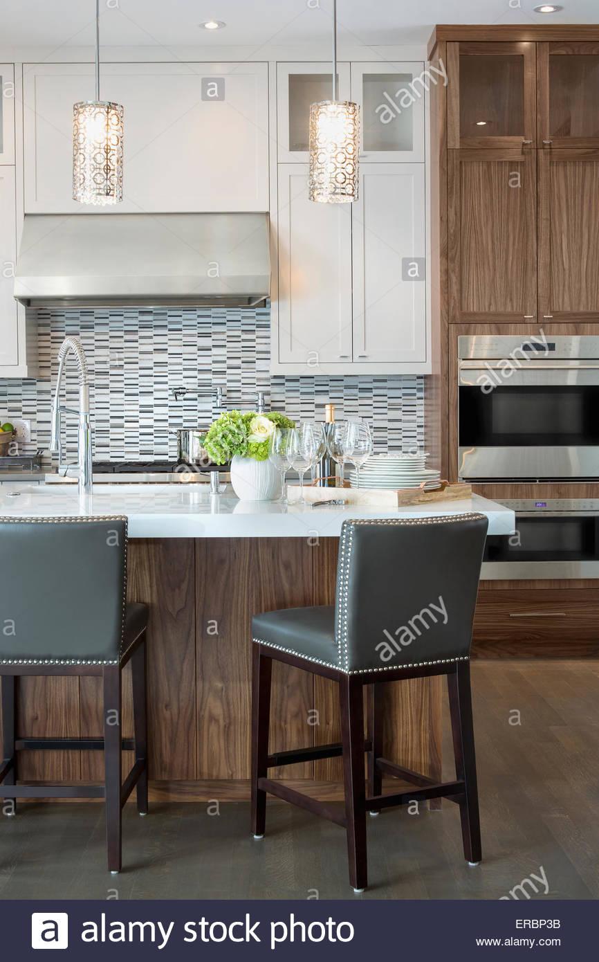 Le luci pendenti sulla moderna cucina bianca Isola Immagini Stock