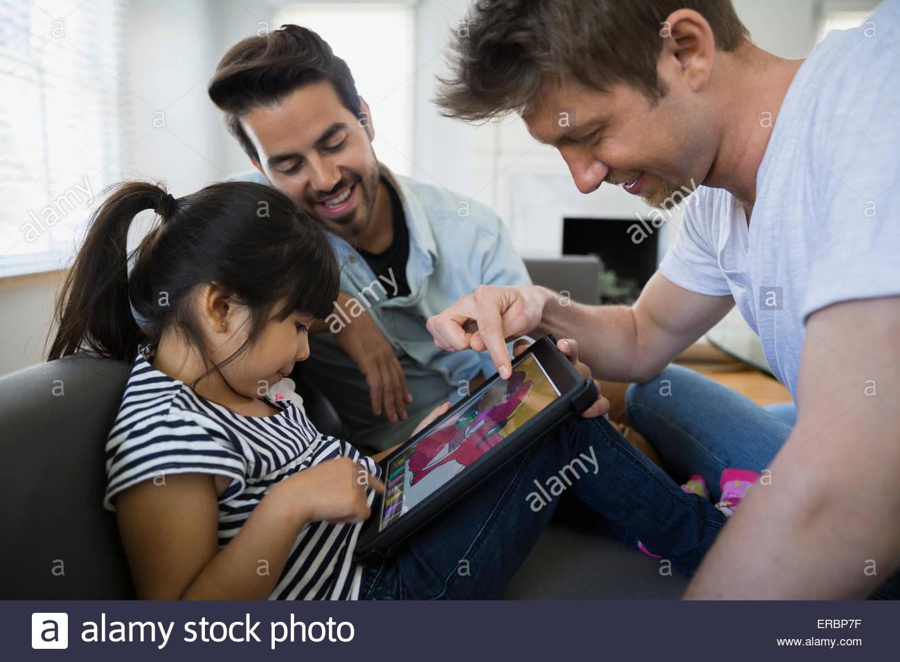 Coppia omosessuale e la figlia con tavoletta digitale Immagini Stock