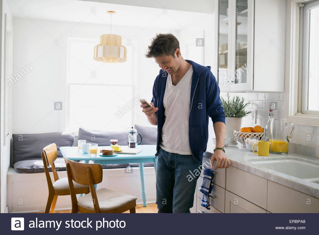 Uomo informale texting con un telefono cellulare in cucina Immagini Stock