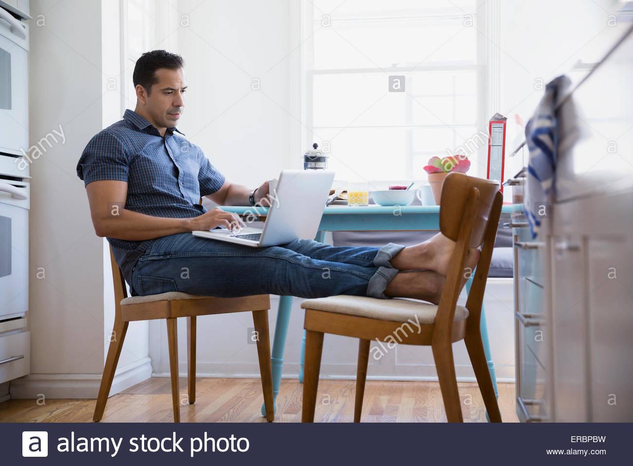 Brunette uomo utilizzando i piedini del portatile fino tavolo da cucina Immagini Stock