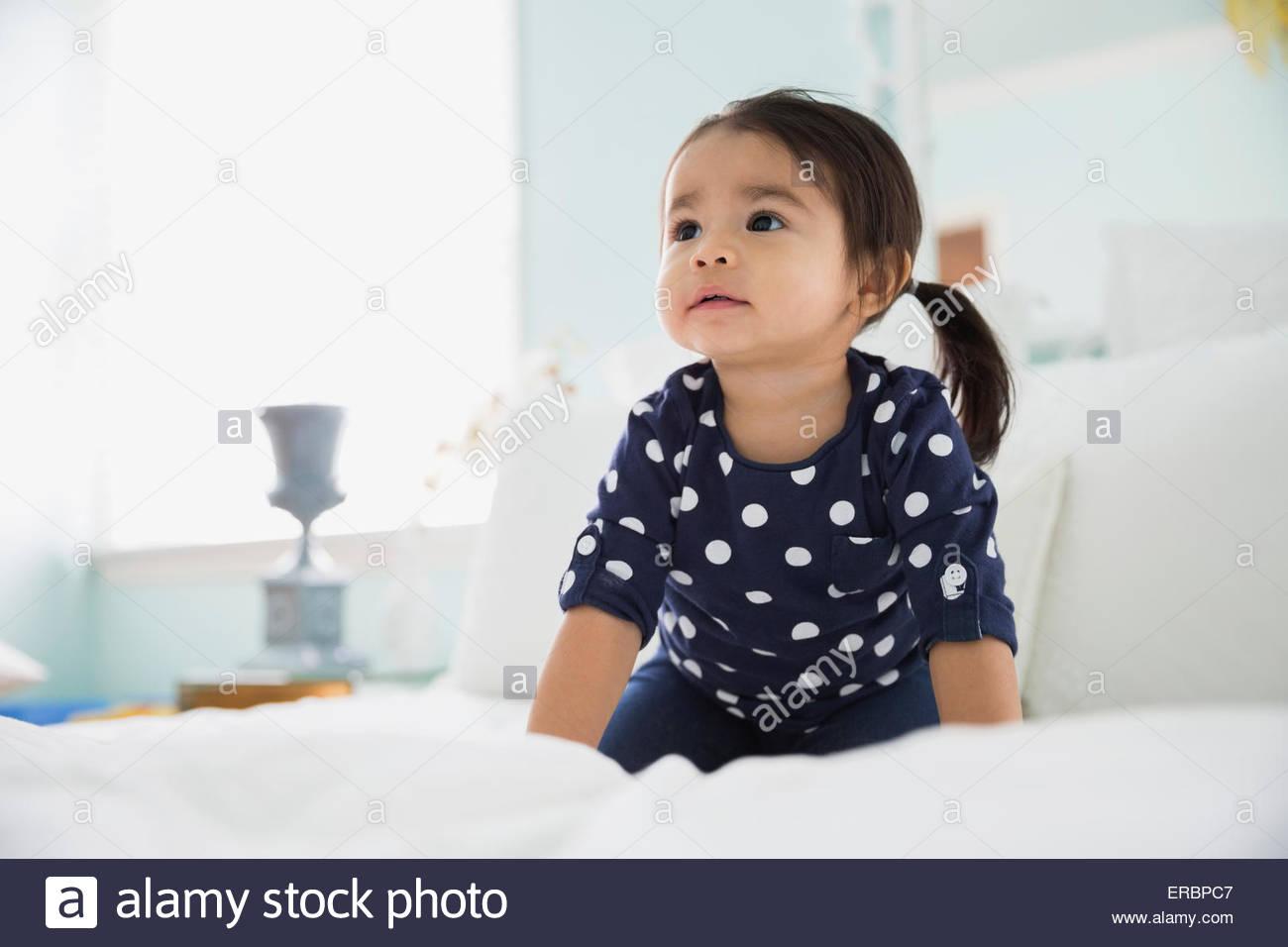 Curioso brunette girl cercando sul letto Immagini Stock