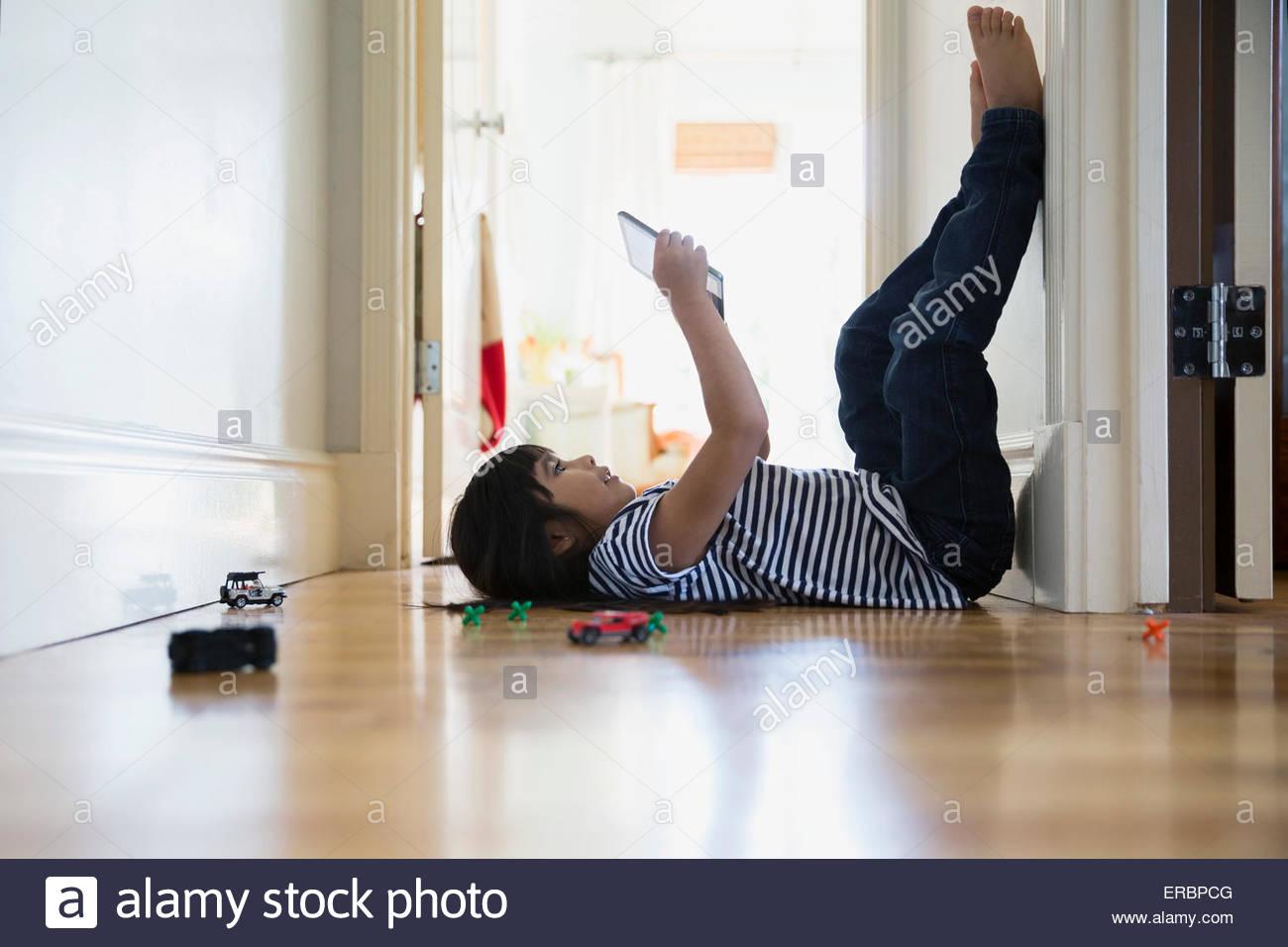 Bruna ragazza utilizzando tavoletta digitale delle gambe fino a parete Immagini Stock