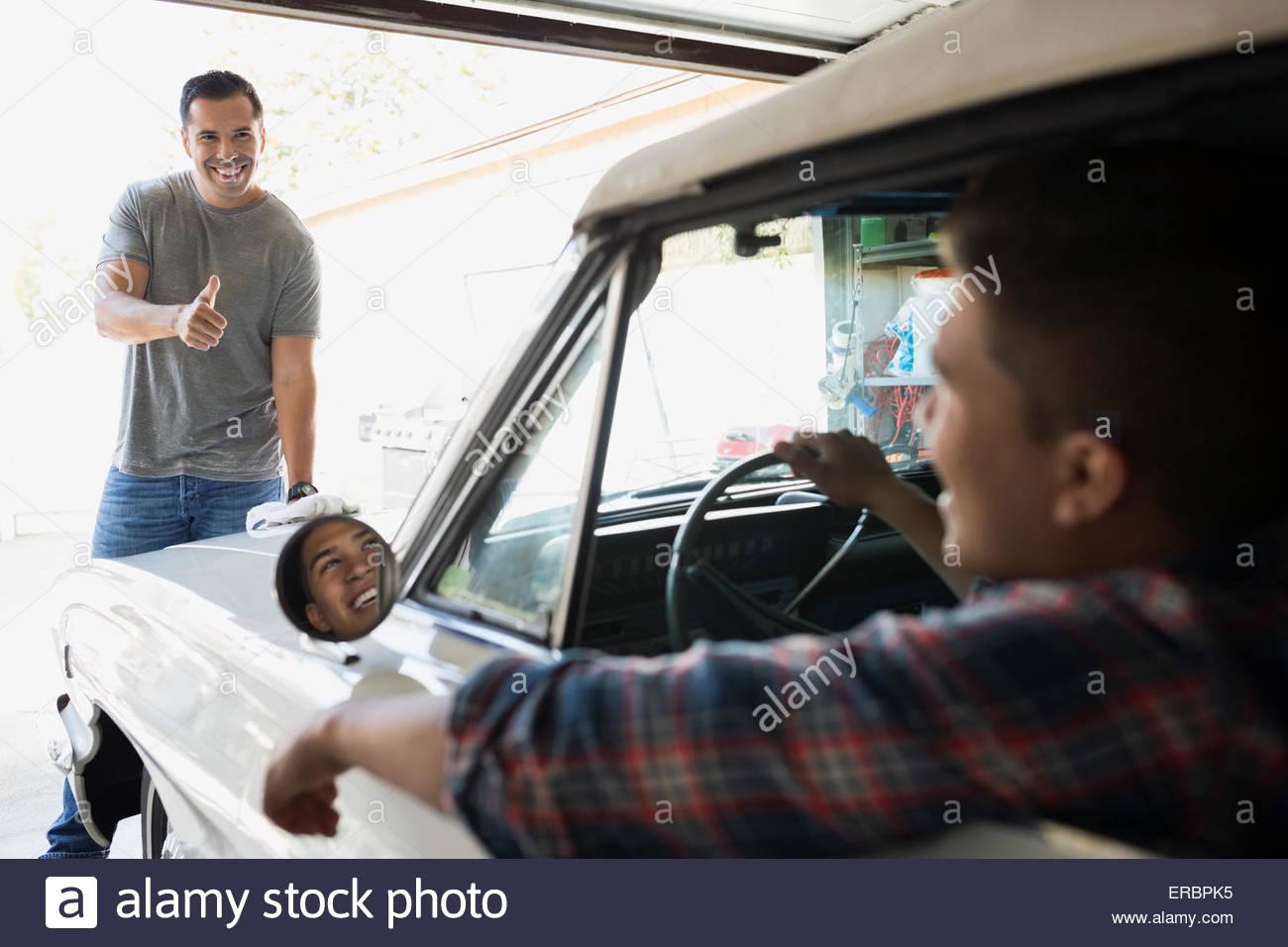 Padre dando il figlio in auto d'epoca, pollice in alto Immagini Stock