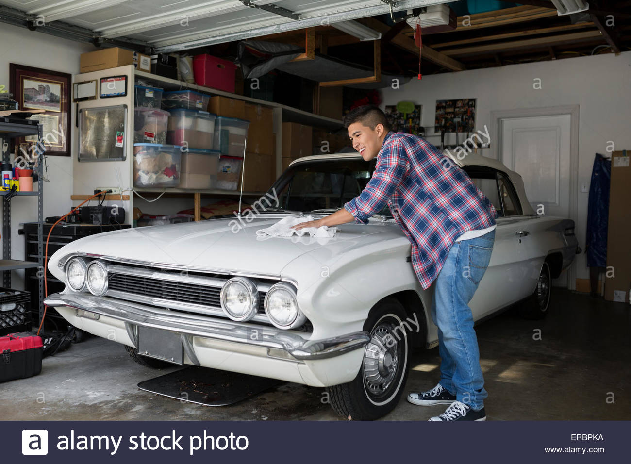 Giovane uomo ceretta vintage auto in garage Immagini Stock