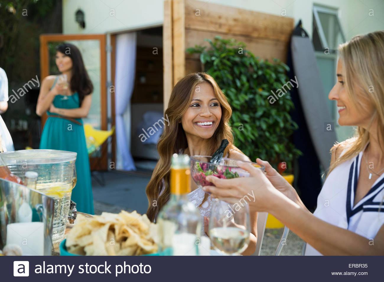 Gli amici di mangiare e passando il cibo in tavola patio Immagini Stock