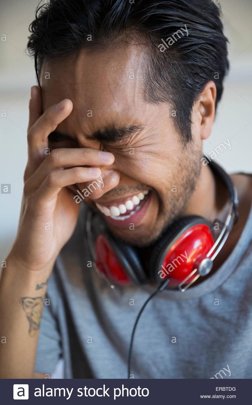 Uomo con le cuffie a ridere con testa in mani Immagini Stock
