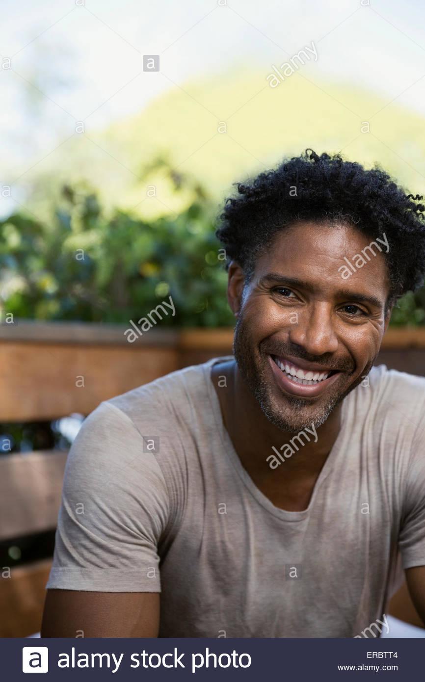 Ritratto uomo sorridente con ricci capelli neri all'aperto Immagini Stock
