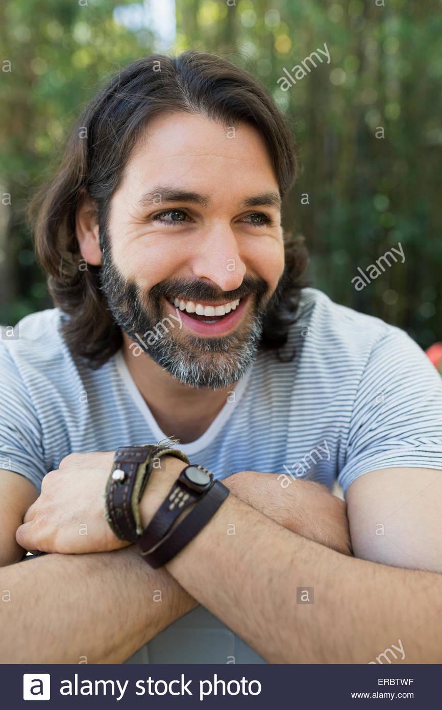 Close up ritratto sorridente uomo barbuto che guarda lontano Immagini Stock