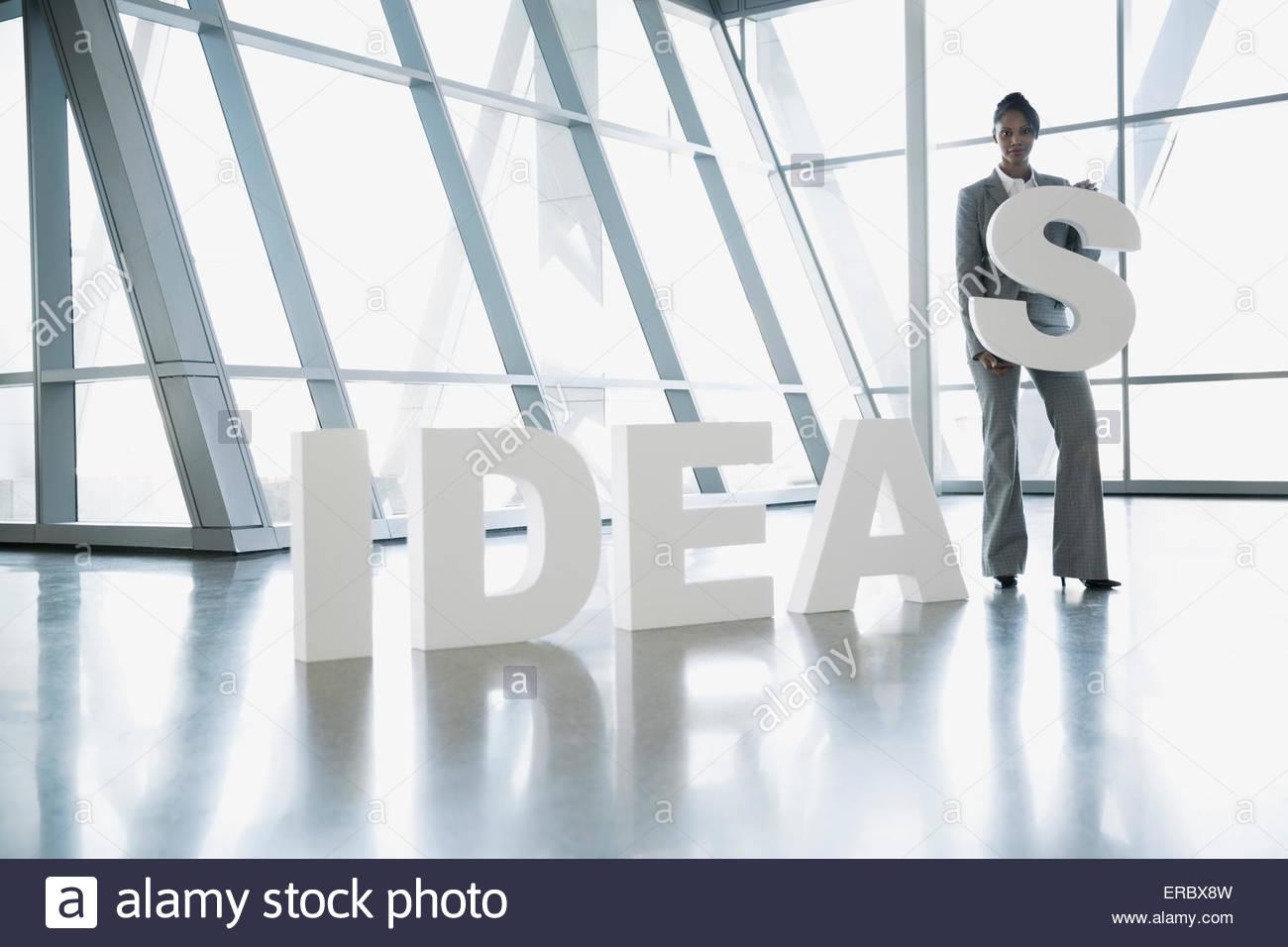 Ritratto imprenditrice tenendo la lettera S in 'Idee' Immagini Stock