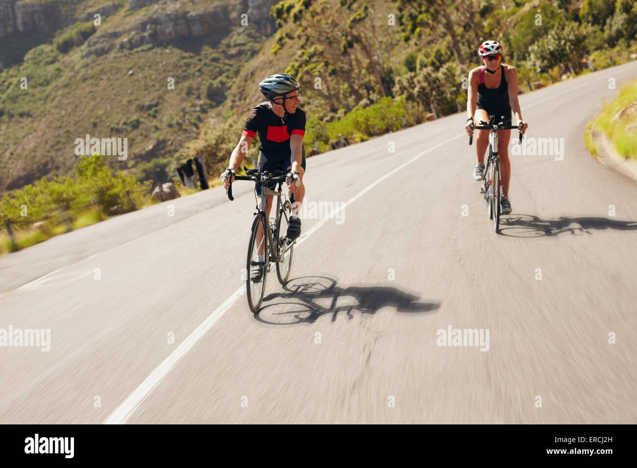 Due ciclista la pratica per la gara di triathlon. Triatleti praticare ciclismo su strada di campagna. Uomo e donna Immagini Stock