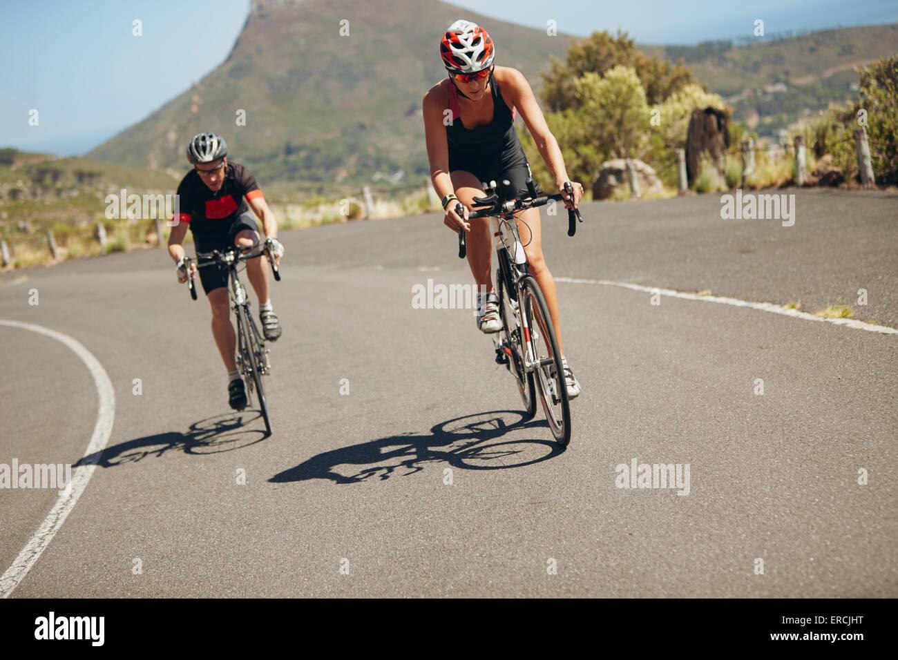 Ciclista equitazione biciclette su strada aperta. Triatleti escursioni in bicicletta giù per la collina su Immagini Stock