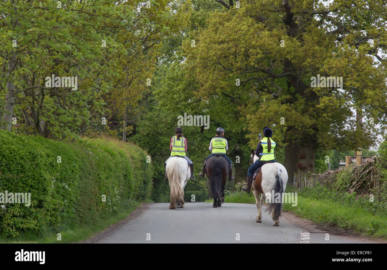 Cavallo femmina piloti su un vicolo del paese con giacche ad alta visibilità, England, Regno Unito Immagini Stock